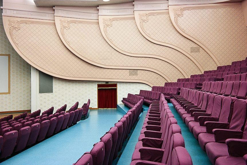 Colour photograph of the side view of the National Drama Theatre in Pyongyang featuring imperial purple coloured seats.