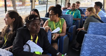 A bus carries members of the local PNG and international media. All are wearing lanyards.