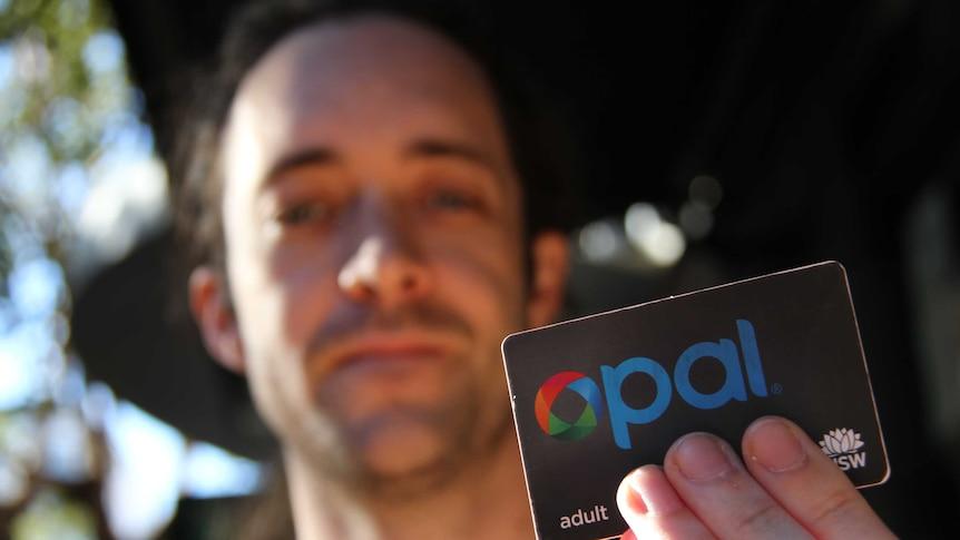 A man holding up an opal card.