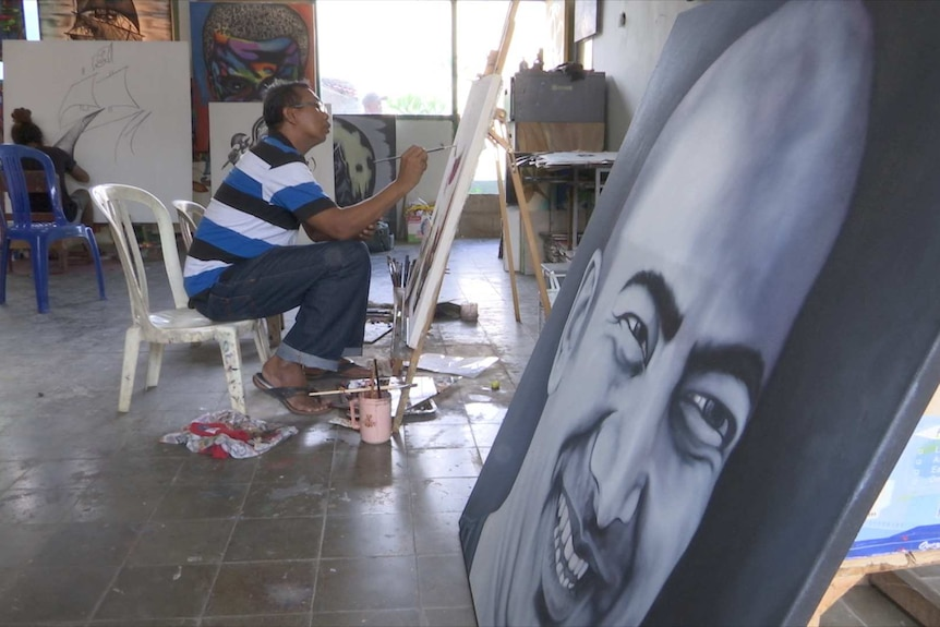 Man sits on plastic chair painting with portrait in foreground
