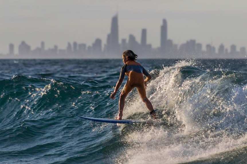 A young surfer catches a wave on the Gold Coast