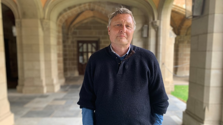 A portrait of Bernd Bartl smiling and standing under a prestigious-looking sandstone archway at the University of Melbourne.