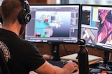 A video game designer works on a computer, with illustrations on the screen