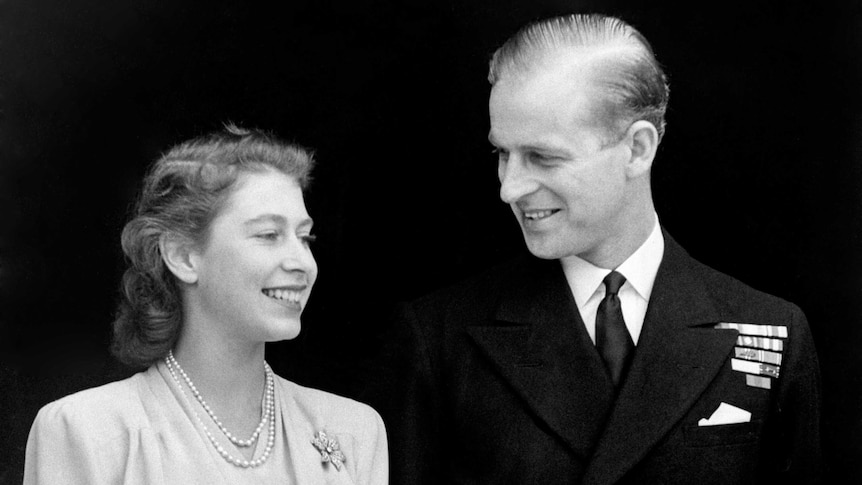 A black and white photo of Princess Elizabeth and Philip Mountbatten smiling as they stand side by side.