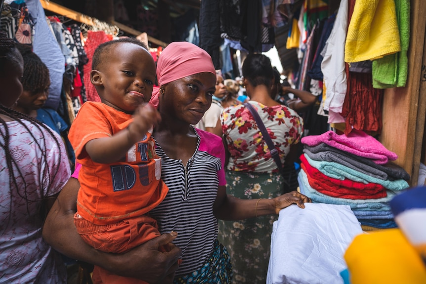 A woman holds her son in a clothing market.