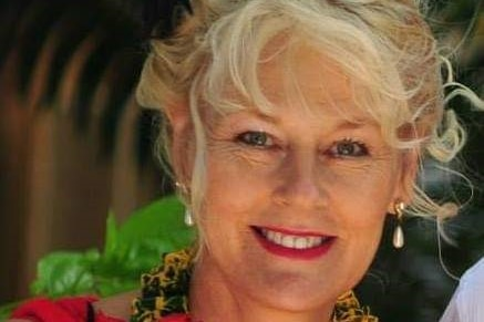 A middle-aged woman with blonde curly hair and pearl earrings smiles broadly.