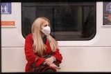 A woman in a red coat sitting on a train wearing a protective face mask.
