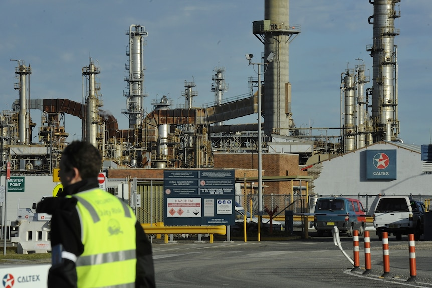 Worker stands outside Caltex oil refinery in Kurnell