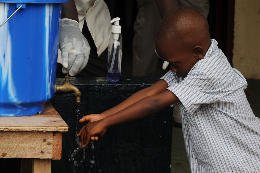 A child washes their hands with chlorine and water in Monrovia, the capital of Liberia.
