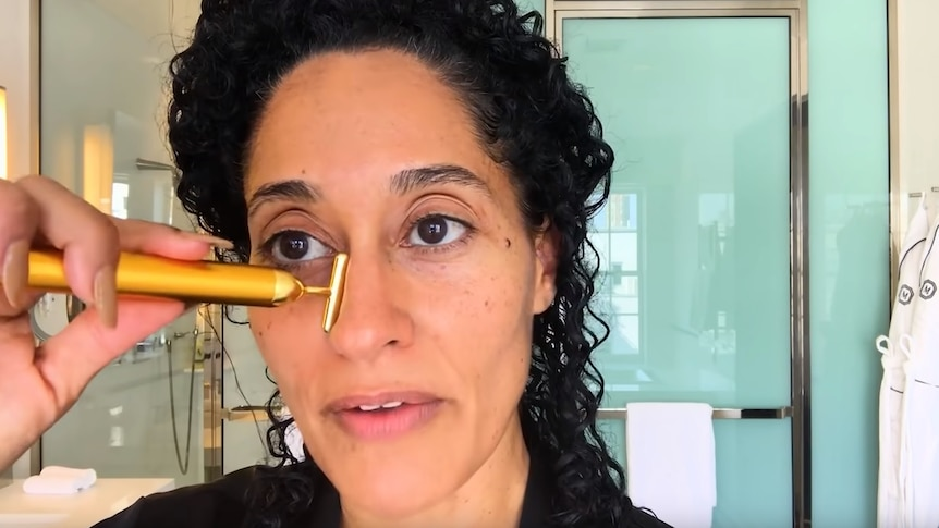 Woman in bathroom places small face massager on her face