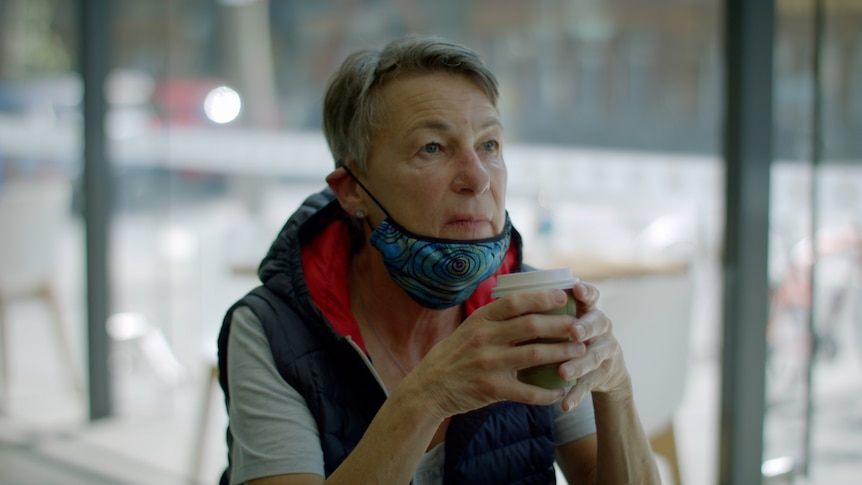 A woman sits, staring off into the distance, holding a cup of coffee