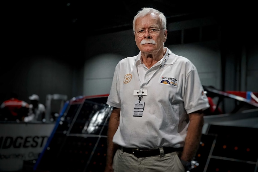 Man with white hair and white moustache stands in front of a solar car.