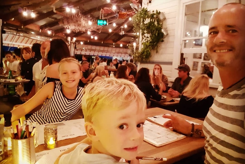 A man and two young children at a table on the deck of a busy restaurant at night time.