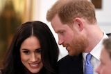 Prince Harry turns to Meghan Markle, speaking in her ear, as she smiles.