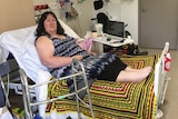 A woman on a bed in a hospital room with a walker next to her.