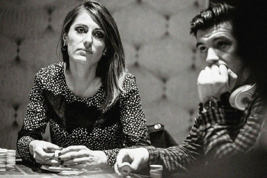 Black and white image of Alex O'Brien sitting at table holding poker chips, with man seated to her right holding.