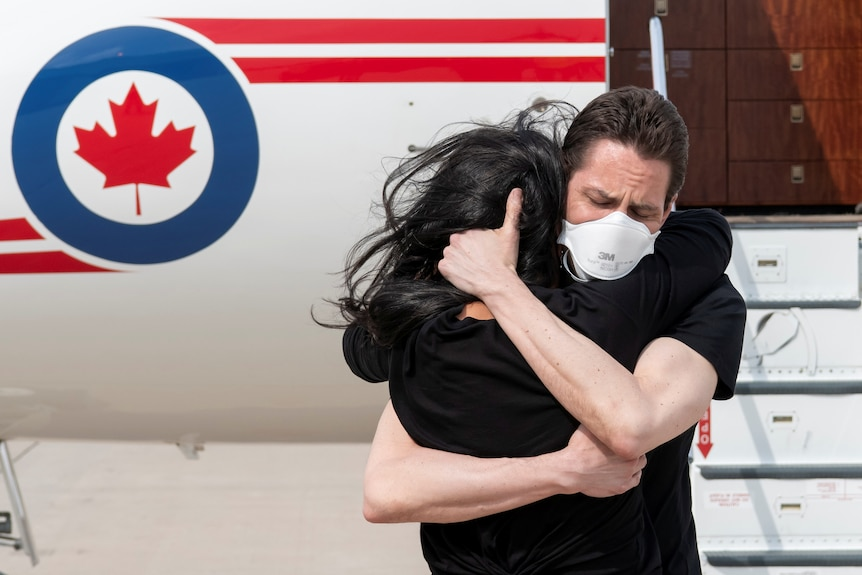 A man in a mask hugs his wife in front of a plane.
