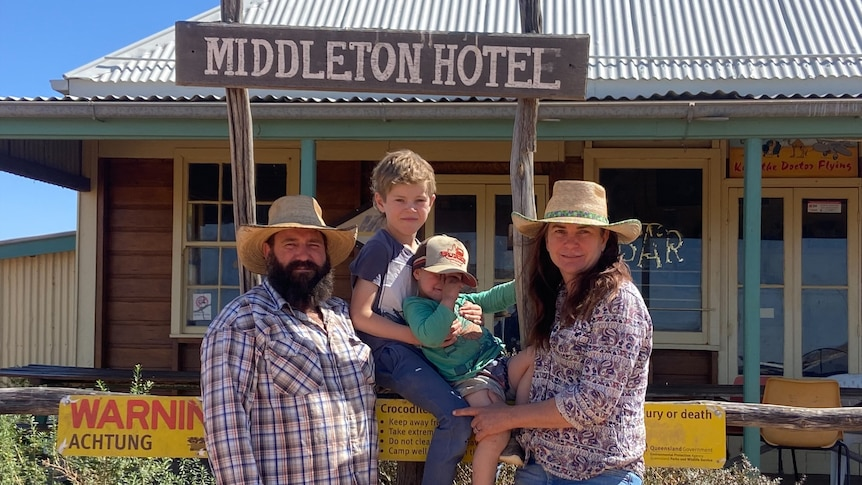 A family of four pose for a family picture in front of an old outback pub, under a sign that says Middleton Hotel.