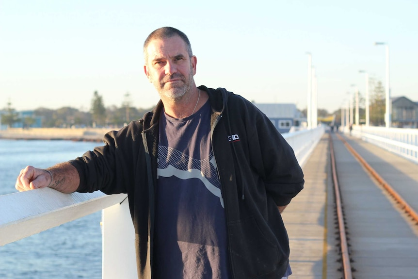 Jon Eddy, A 50-year-old man in a black t-shirt and fleece jacket, standing on a long timber jetty. It's early morning.