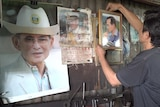 Thai metal worker hangs up portraits of the royal family.