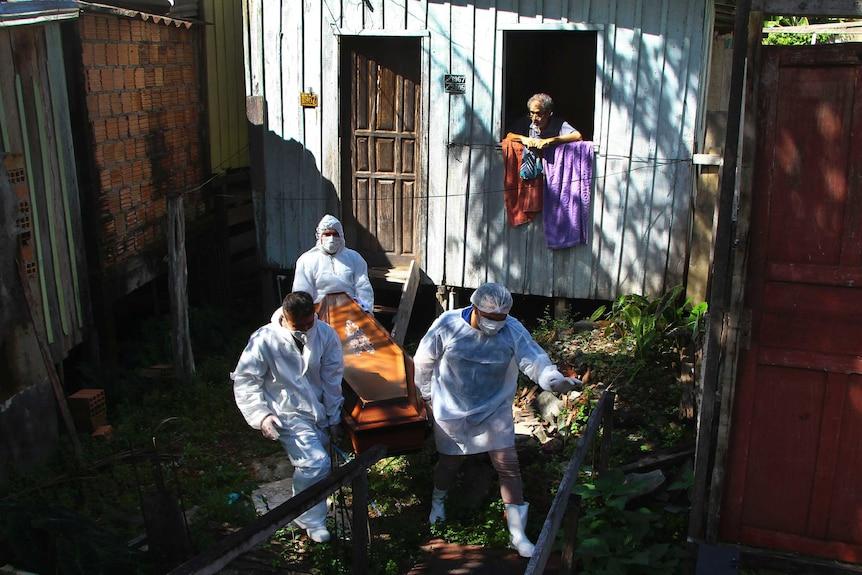 Public funeral service workers remove the body of 94-year-old woman who died from complications related to COVID-19.