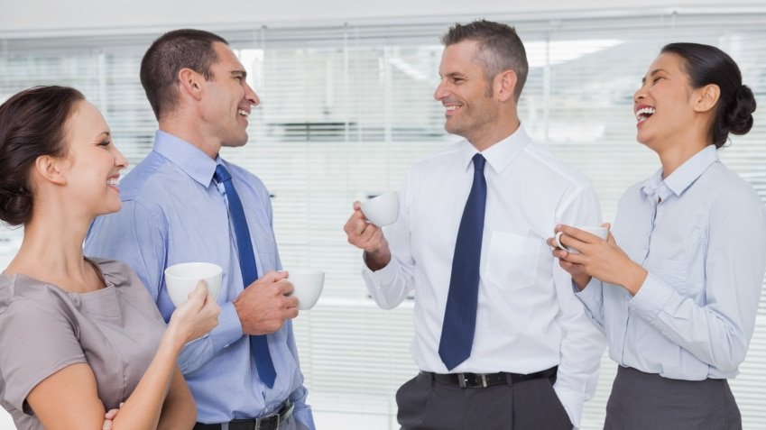 Office workers standing around and joking while holdings cups of coffee.