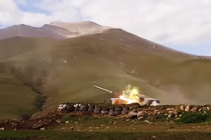 A still image of a missile being shot from a tank with mountains in the background.