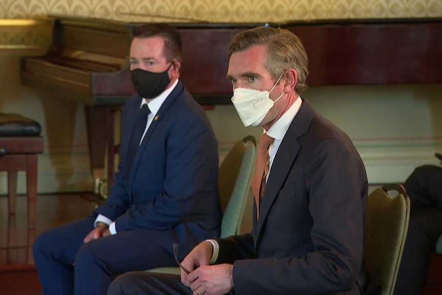 Two men sitting with masks on.