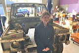 teenage girl standing in front of a stripped back Range Rover car.