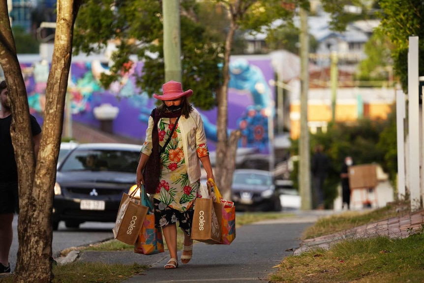 Woman wearing mask walks home with groceries in a street at Brisbane's West End before lockdown started.