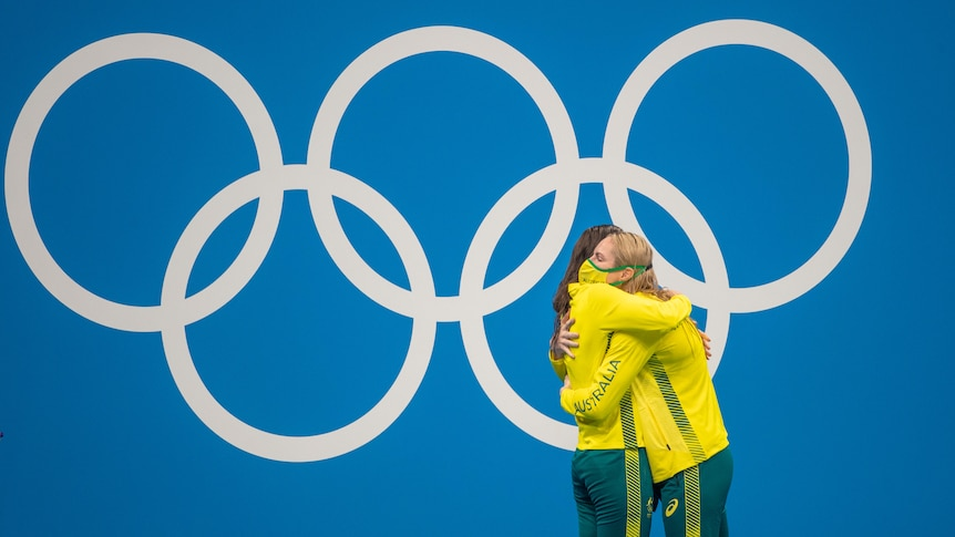 Australian swimmers Emily Seebohm and Kaylee McKeown hug on the dais at the Tokyo Olympics, with the Olympic rings behind them.