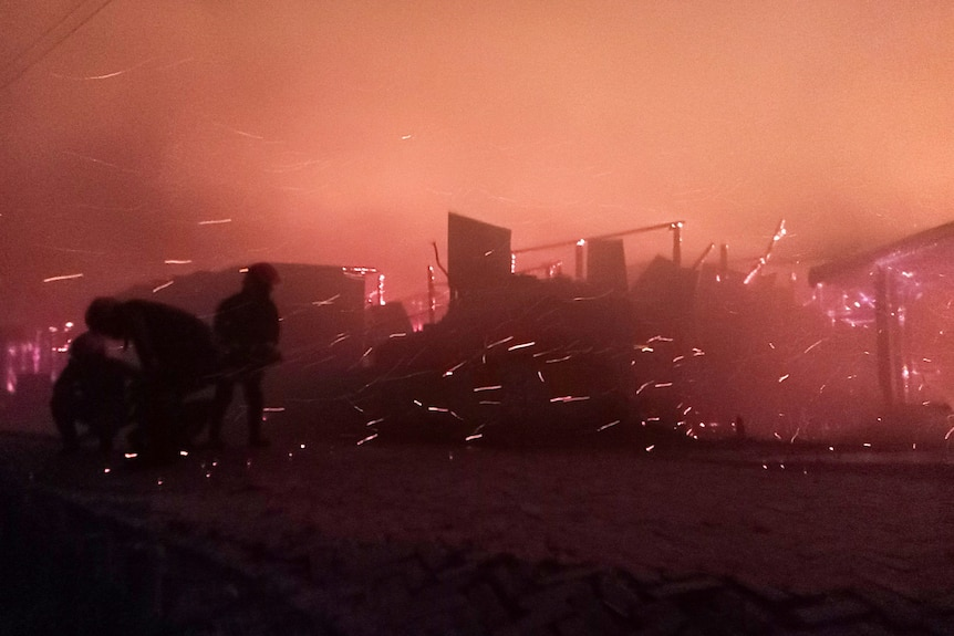 A night-time shot of a brightly lit fire with sparks of flames in shanty town.