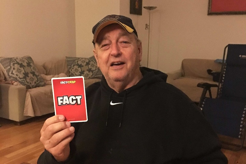 "A older man holds up a card saying ""Fact"""