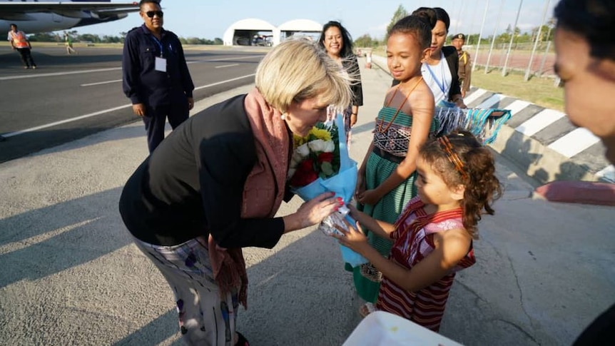 Julie Bishop leans down to accept flowers from a young girl.