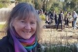 Samantha Dunn outside holding a carton of plants.