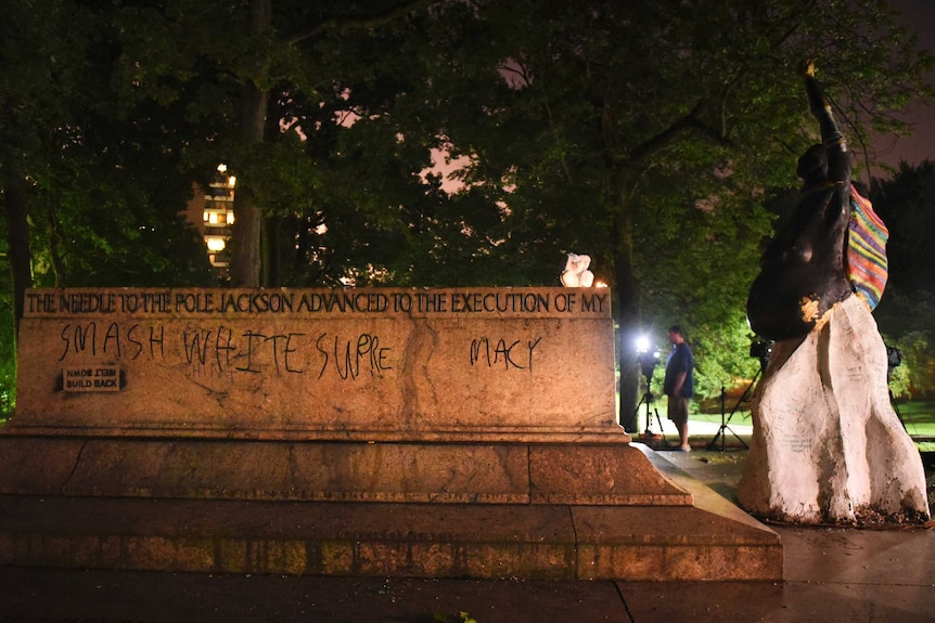 """The empty pedestal of the Jackson and Lee monument with the words """"smash white supremacy"""" written on it."""