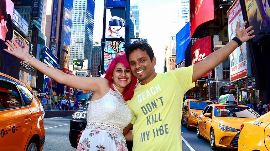 Meenakshi Moorthy, with bright pink hair, and her husband Vishnu Viswanath smile at the camera with their arms around each other