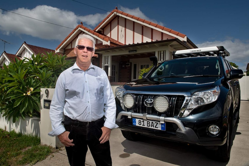 Max Bancroft at home in his front yard standing next to his Toyota Prado.