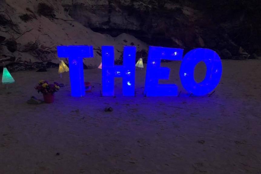 Blue neon blocks spelling 'Theo' in sand.