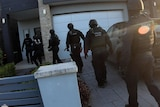 Police officers outside a house
