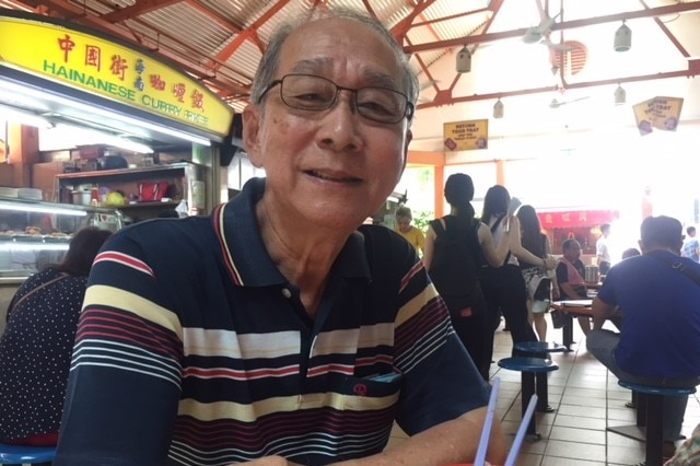 An older man with grey hair and glasses sits in a covered food-court looking at the camera with a half-smile