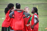 Girls huddled together on their soccer field.
