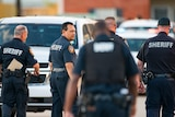 Sheriff looks over his shoulder, surrounded by other police officers at a crime scene.