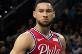 Ben Simmons is mean-mugging after a dunk. LeBron James looks frustrated behind him.