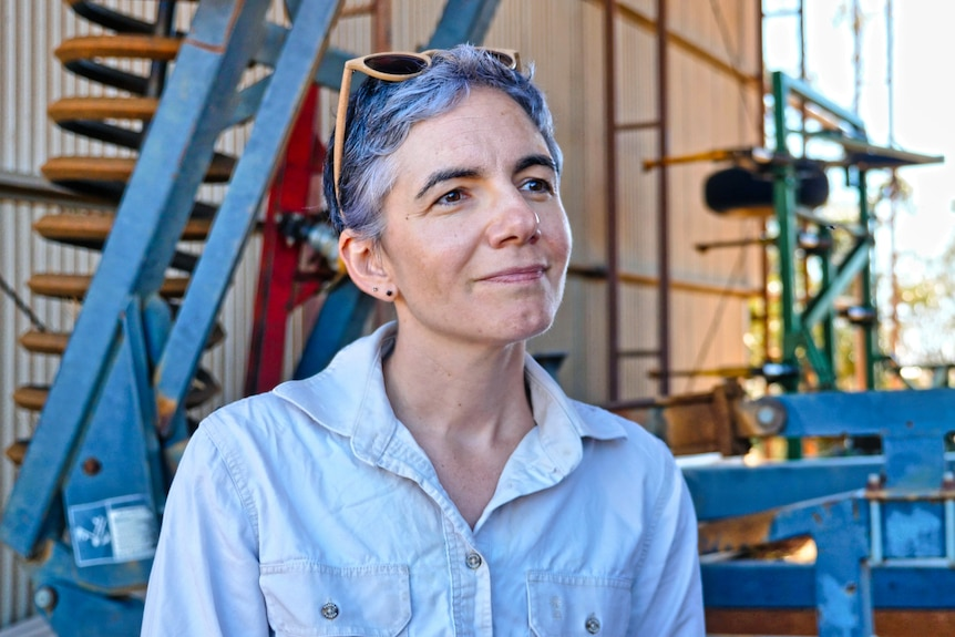 A head and shoulders shot of a woman in front of a shed on a farm.