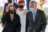 Kamala Harris walks alongside Singapore's Prime Minister Lee Hsien Loong with a uniformed local officer behind.