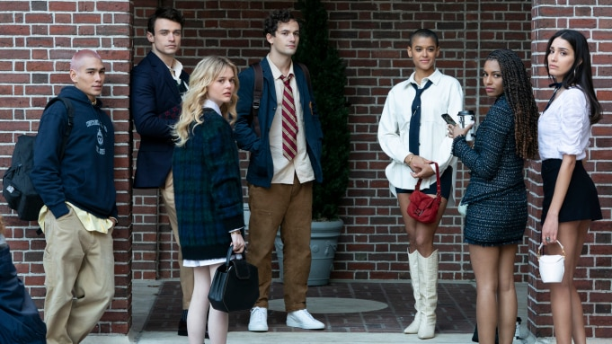 A group of seven teens stand against a brick wall, looking back at the camera.