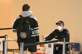 A police officer in a mask speaks to a man in a hoodie and with a backpack