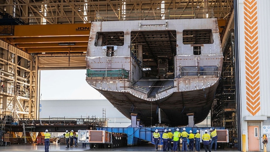 The hull of an huge ship sits inside a warehouse.