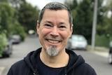 Ed Moreno smiles while standing on a suburban street.